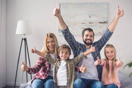Photo pour Portrait de famille heureuse montrant les pouces vers le haut et regardant la caméra à la maison - image libre de droit