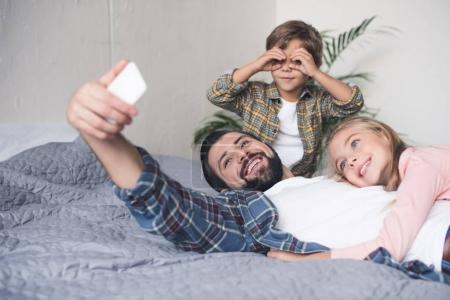 father and kids taking selfie