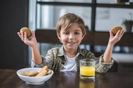 Photo for Portrait of smiling little boy looking at camera during breakfast at home - Royalty Free Image