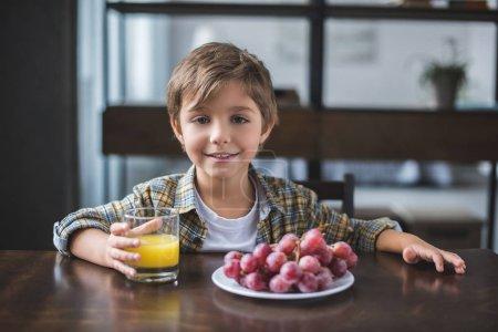 Photo pour Portrait de petit garçon souriant regardant la caméra pendant le petit déjeuner à la maison - image libre de droit