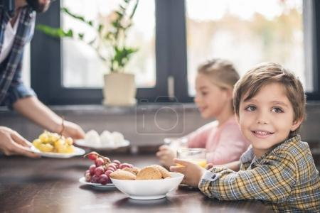 Photo for Selective focus of smiling little boy having breakfast with family at home - Royalty Free Image
