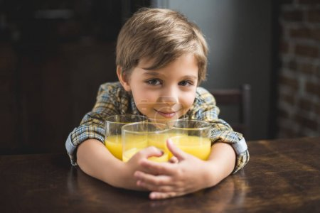 child at table with glasses of juice