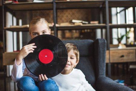Photo pour Vue obscurcie des enfants avec disque vinyle regardant la caméra à la maison - image libre de droit
