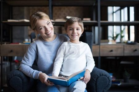 Photo for Portrait of smiling mother and cute son with book looking at camera at home - Royalty Free Image