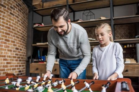 father and daughter playing table football