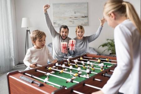 Photo pour Parents avec pop corn, je regarde les enfants jouer au football de table à la maison - image libre de droit