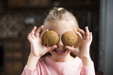 Photo for Obscured view of smiling child covering eyes with cookies in hands at home - Royalty Free Image