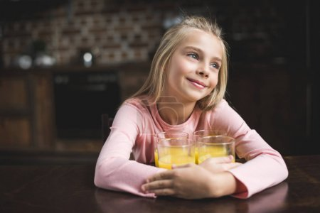Photo for Portrait of little cute girl sitting at table with glasses of juice at home - Royalty Free Image