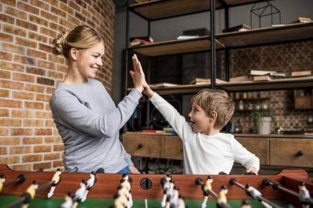 mother and son playing table football