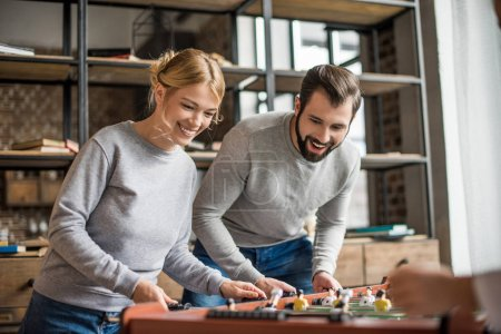 couple playing table football at home