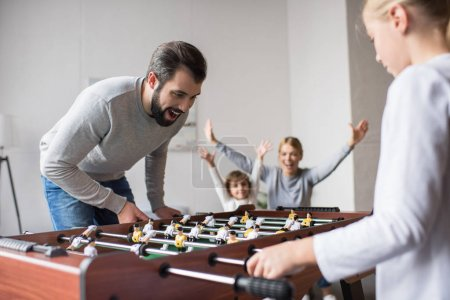 Photo for Young family playing table football together at home - Royalty Free Image