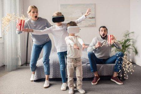 Photo pour Parents avec pop corn, je regarde les enfants qui jouent dans le vr casques d'écoute à la maison - image libre de droit