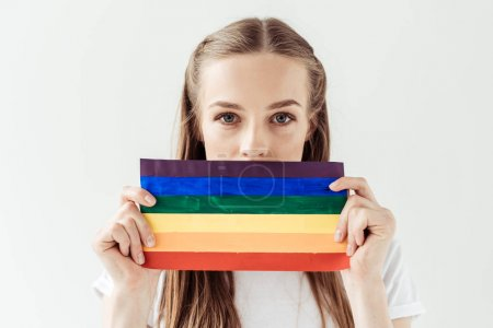 Photo for Young woman covering her mouth with small rainbow flag isolated on white - Royalty Free Image