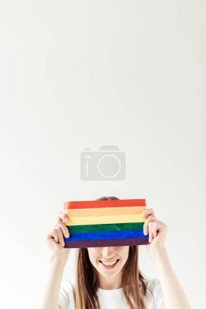 Photo for Young woman covering her forehead with small rainbow flag isolated on white - Royalty Free Image