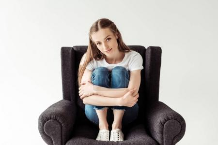 Girl sitting on armchair