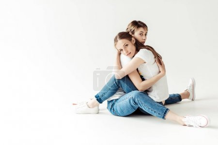 Lesbians hugging and sitting on floor