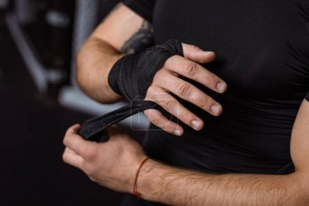 Boxer wrapping hand with bandage