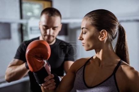 Photo for Selective focus of male trainer wrapping boxing glove to beautiful young sportswoman - Royalty Free Image