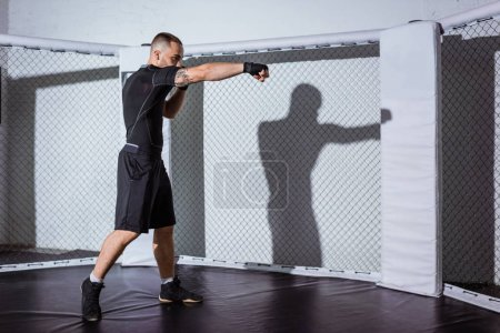 Photo for Full length view of muscular young fighter training and looking away - Royalty Free Image