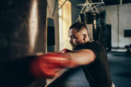 Photo pour Foyer sélectif du jeune sportif dans l'entraînement des gants de boxe avec sac de boxe - image libre de droit