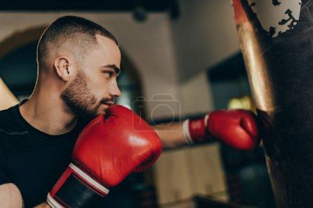 Photo pour Vue côté gros plan musculaire jeune boxeur formation avec sac de boxe - image libre de droit