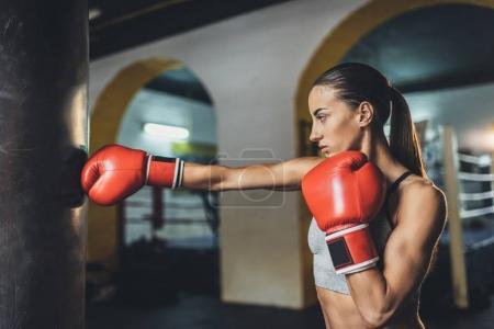 Photo pour Vue latérale du jeune boxeur féminin de formation avec le sac de boxe - image libre de droit