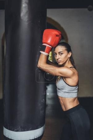 Photo pour Belle jeune boxeur féminin se penchant au sac de boxe et regardant la caméra - image libre de droit