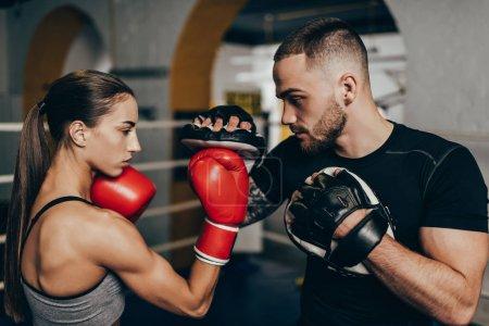 Photo pour Vue de côté de jeunes boxeurs masculins et féminins de formation sur le ring de boxe - image libre de droit