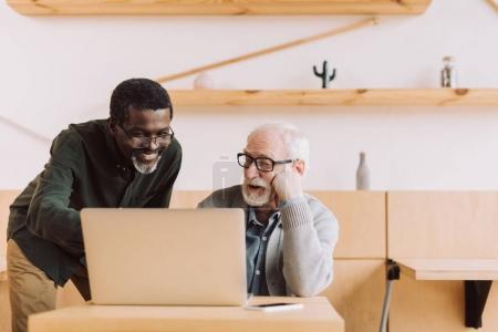 Foto de Multiétnico senior masculino usando laptop juntos - Imagen libre de derechos