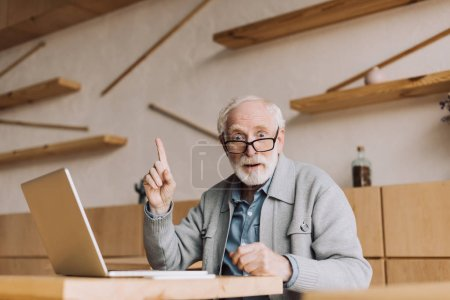 Photo for Surprised senior man with laptop having idea while sitting in cafe - Royalty Free Image