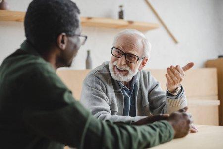 Foto de Hombre mayor hablando con su amigo afroamericano en la cafetería - Imagen libre de derechos