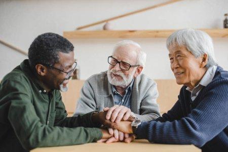 Foto de Grupo de amigos seniors multiétnicos hacer equipo gesto y sonrisa - Imagen libre de derechos