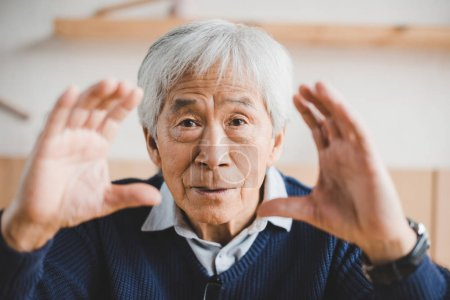 Photo for Senior asian man making frame with hands while looking at camera - Royalty Free Image