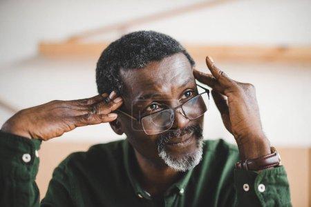 Photo pour Réfléchi homme mûr afro-américain regardant loin et touchant la tête - image libre de droit