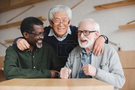 senior friends embracing in bar