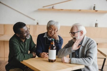 senior friends in bar with bottle of beer
