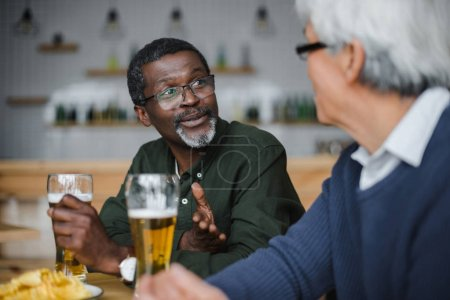 senior friends talking and drinking beer