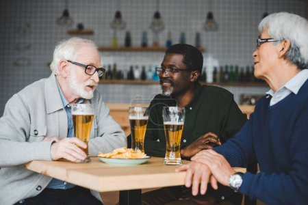 Photo pour Groupe d'amis âgés multiethniques boire de la bière dans le bar - image libre de droit
