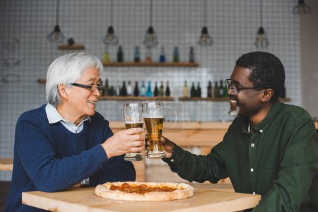 Senior friends clinking glasses of beer