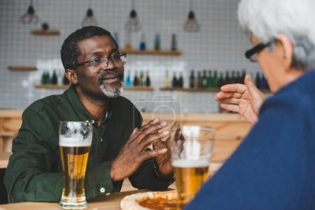 senior friends having discussion at bar