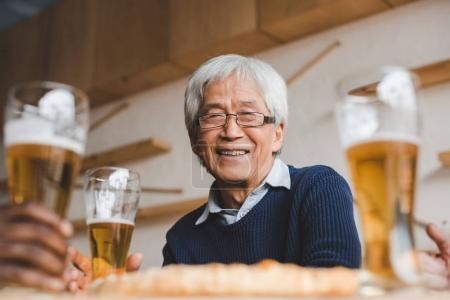 senior asian man in bar with friends