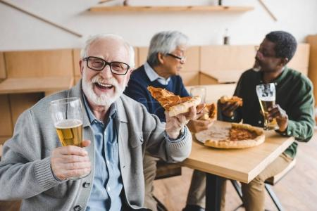 senior man eating pizza with beer