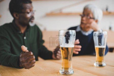 Photo for Senior friends talking at bar while having beer - Royalty Free Image