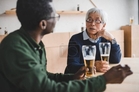 Photo for Senior friends spending time together and drinking beer at cafe - Royalty Free Image