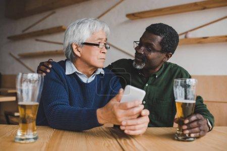 Foto de Sénior hombres bebiendo cerveza mientras asiático hombre mostrando smartphone a amigo - Imagen libre de derechos