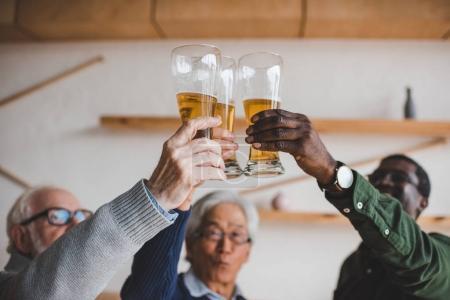 senior friends clinking glasses of beer