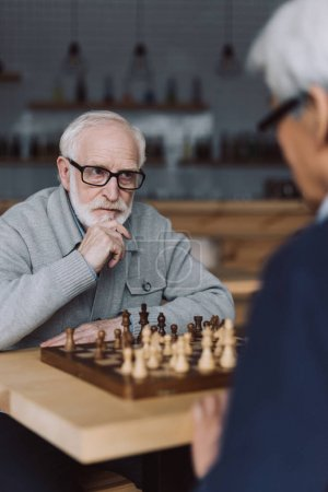Photo for Serious senior man playing chess in cafe and looking at opponent - Royalty Free Image