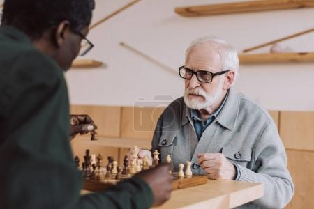 Photo for Concentrated senior man playing chess with african american opponent - Royalty Free Image