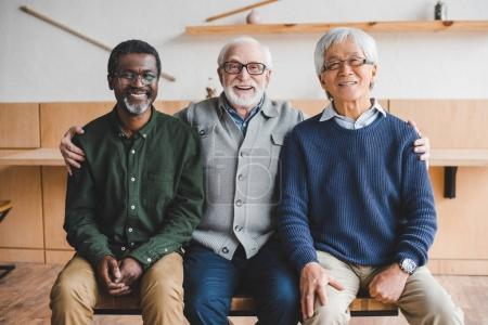 Photo for Group of senior friends embracing and looking at camera - Royalty Free Image