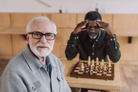 Photo for Senior man playing chess with concentrated opponent touching head - Royalty Free Image